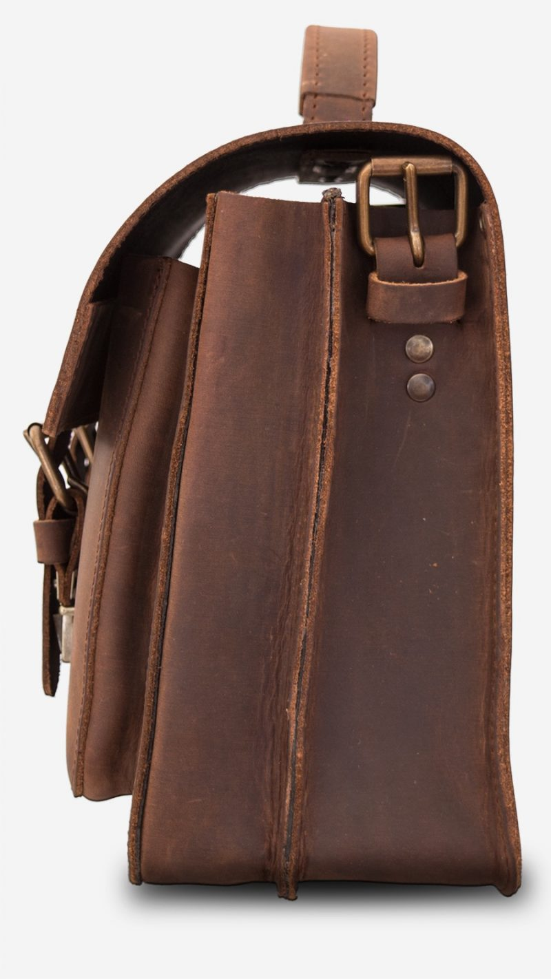Side view of brown leather satchel bag with 2 compartments and 2 front pockets.
