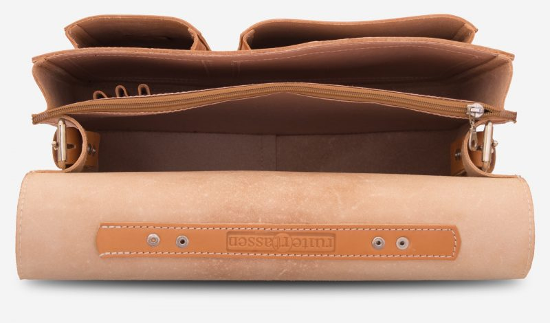 Inside view of the tan leather satchel with 2 main compartments, pen loops and two asymmetric front pockets.