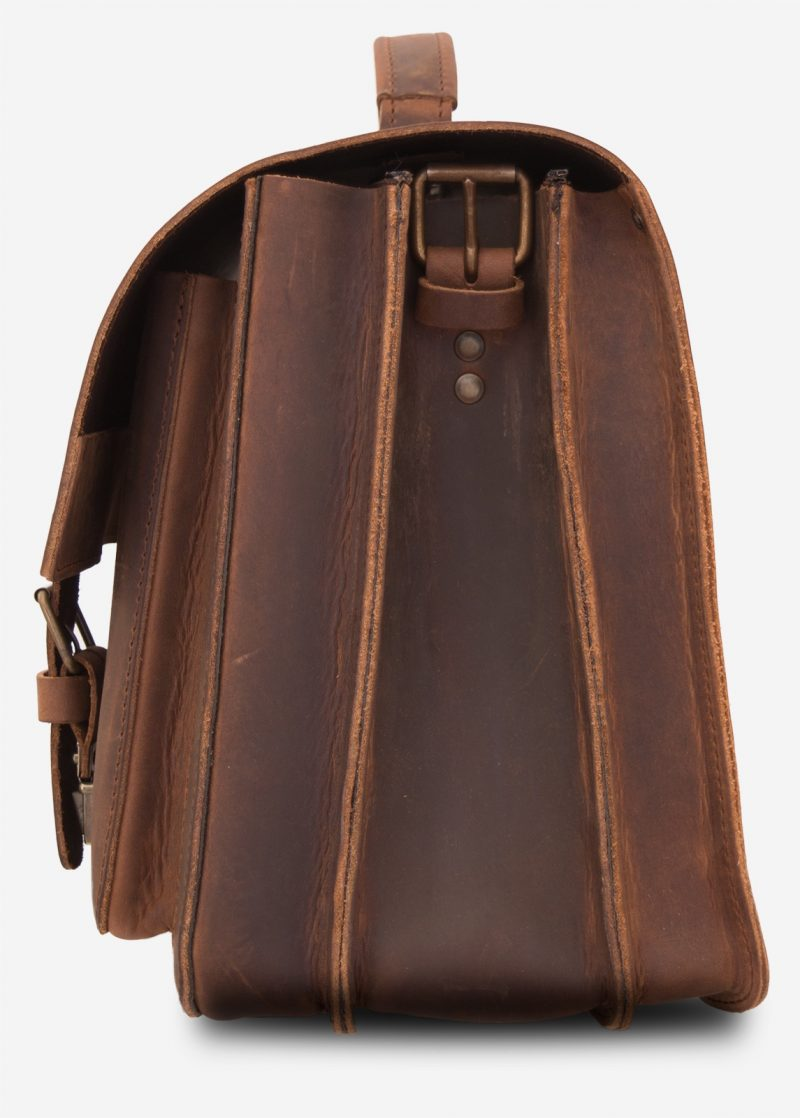 Side view of large brown leather satchel with 3 compartments and front pockets.