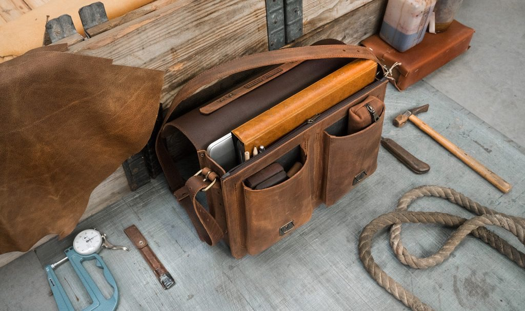 Open brown leather satchel briefcase with a large file, pencil case, book and macbook.