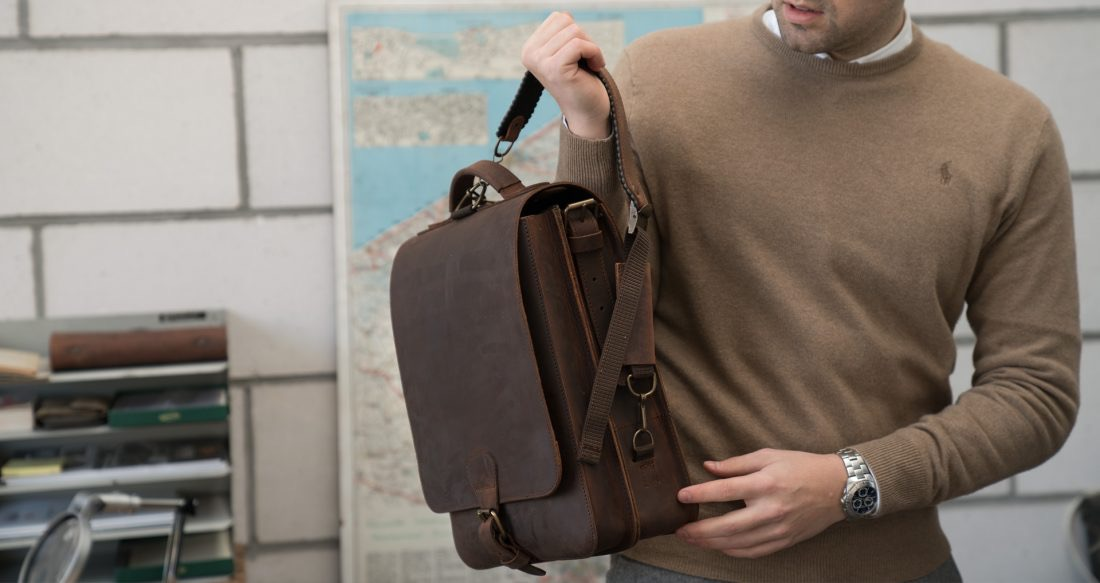 Man wearing the vegetable-tanned brown leather backpack with shoulder straps.