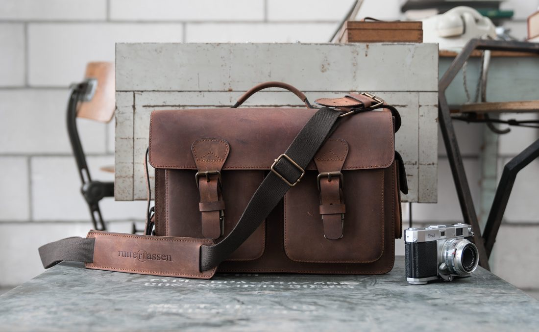 Large brown leather camera bag in photographer office.