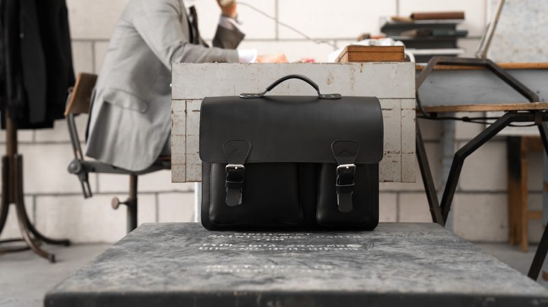 Man in office with black leather laptop satchel bag with 2 gussets and asymmetric front pockets 112337.