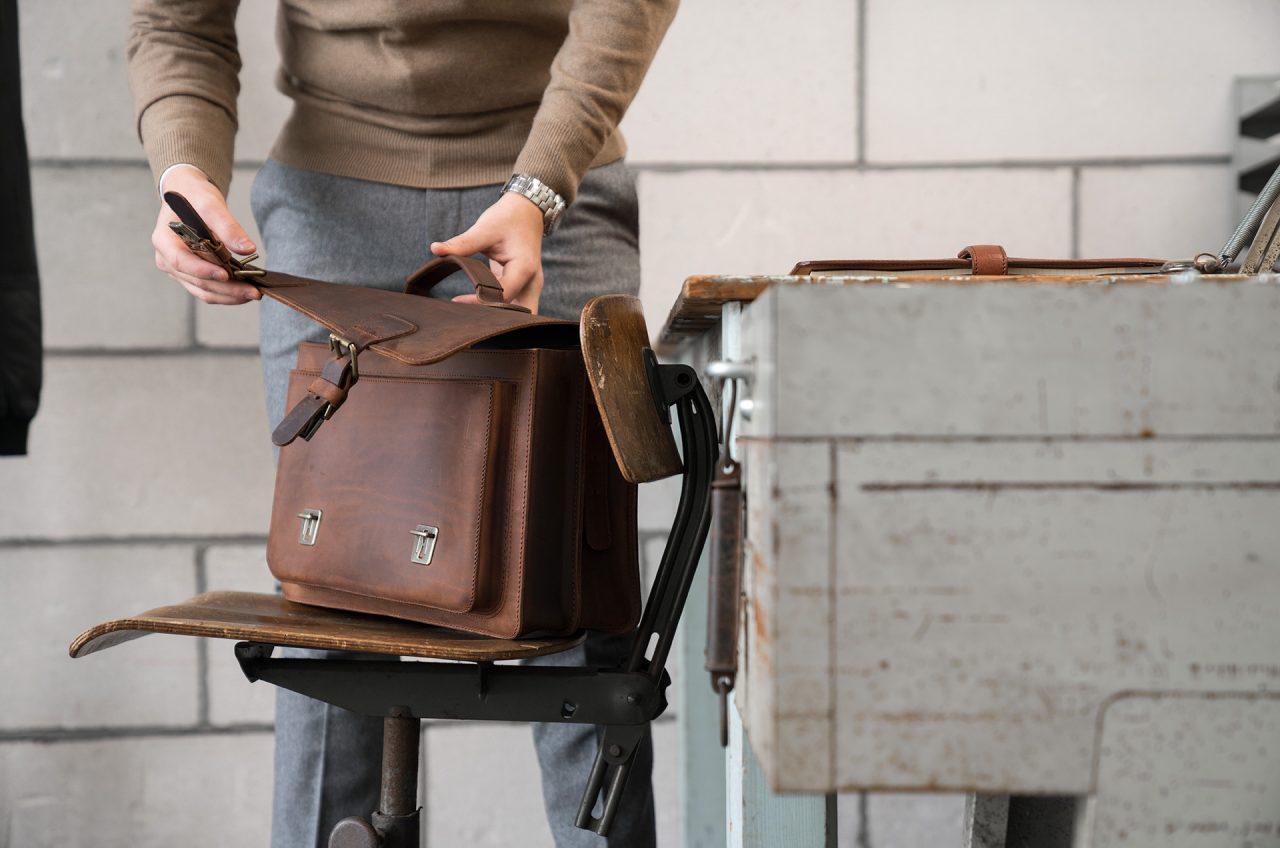 Professor closing his Ruitertassen brown leather satchel.