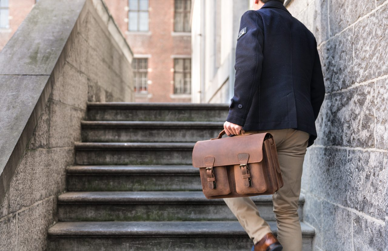 Student with stylish vintage brown leather briefcase on stairs.