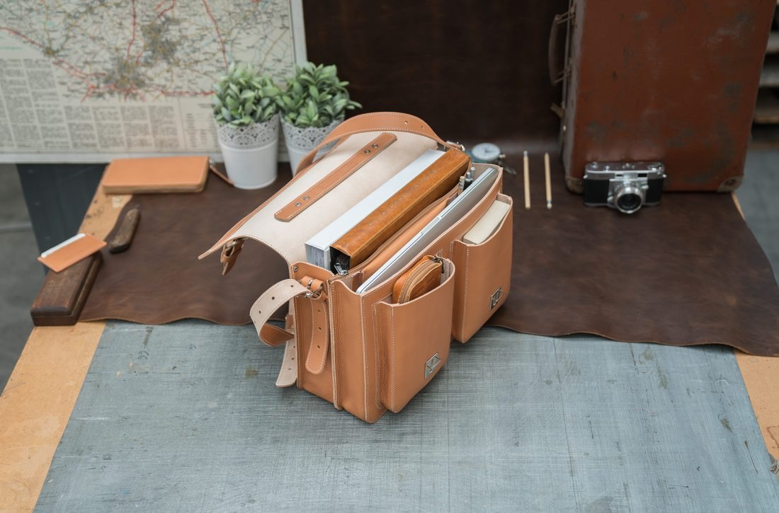 Open tan leather satchel backpack with files and laptop computer.