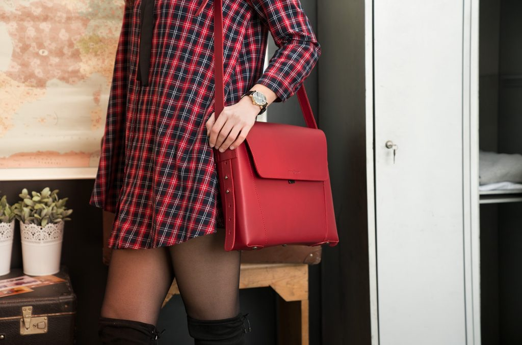 Woman wearing the slim red vegetable-tanned leather briefcase bag on the shoulder.