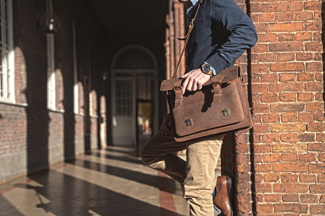 Student with stylish vintage brown leather briefcase at school.