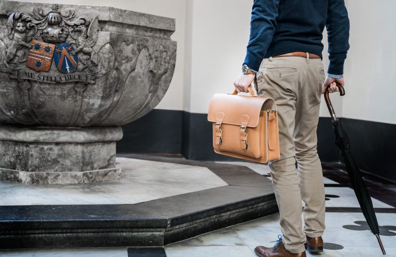 Elegant man holding the tan leather satchel by the handle.