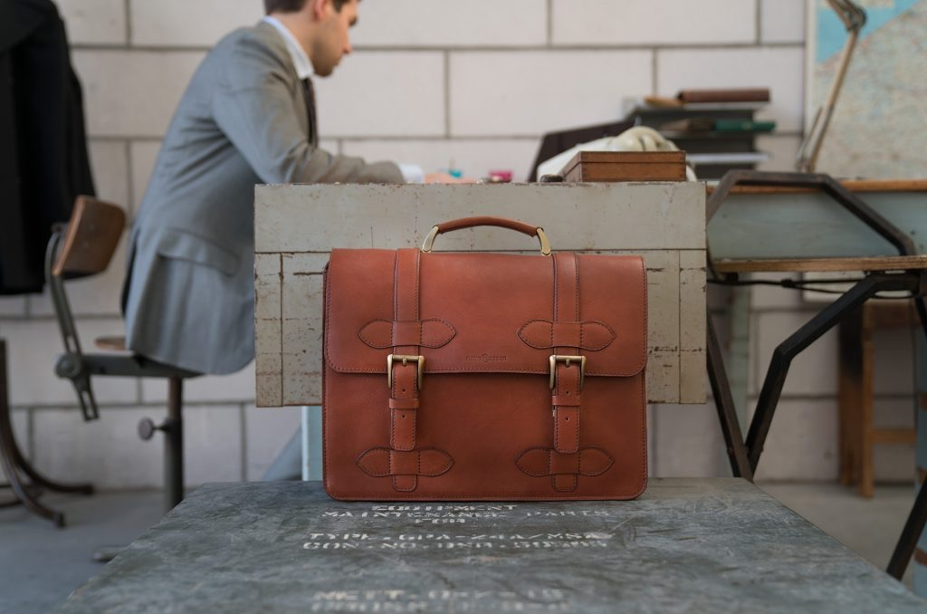 Man in office with the handmade brown vegetable-tanned leather briefcase for men.