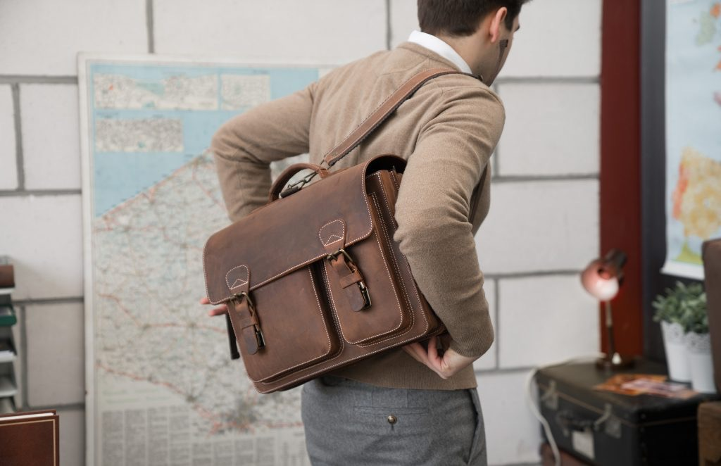 Man carrying his brown leather satchel on the back.