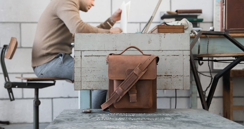 Man in office with the handmade vegetable-tanned brown leather crossbody bag.