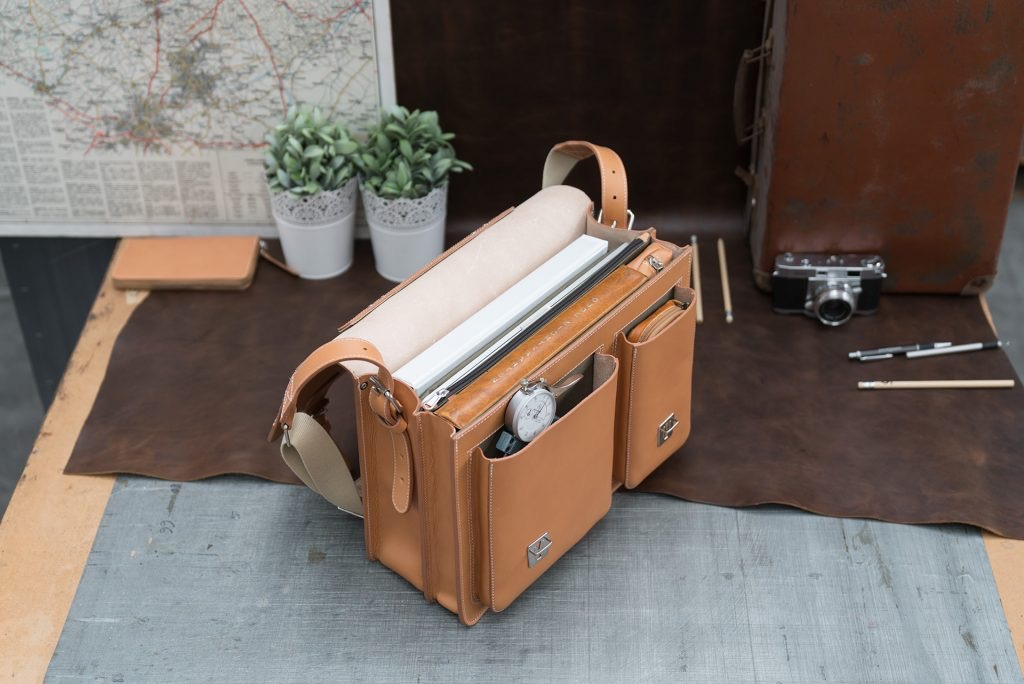 Open full grain tan leather satchel with laptop pocket and folders.
