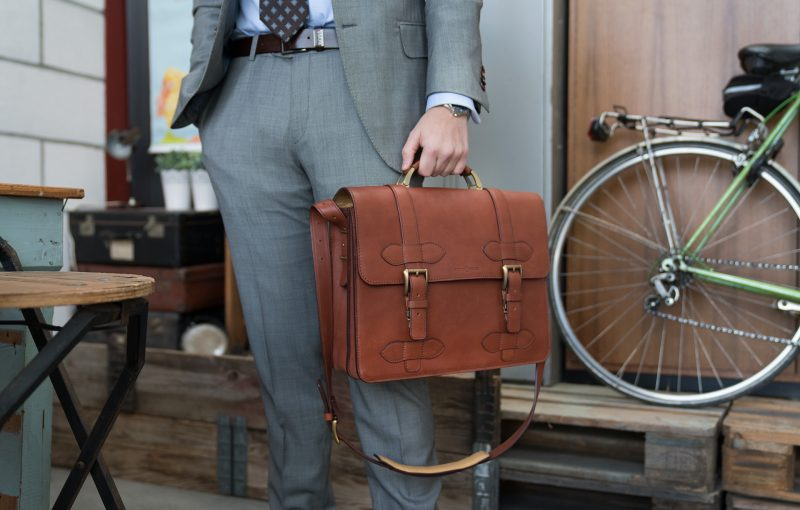 Man wearing the handmade brown vegetable-tanned leather briefcase.