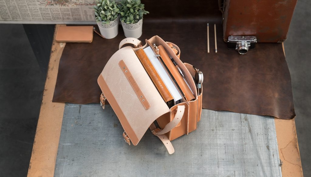 Open full-grain tan leather satchel for professionals with folders and accessories.