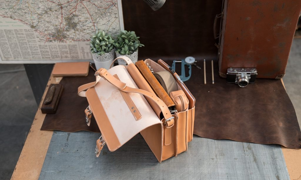 Open student tan leather satchel with files and accessories.