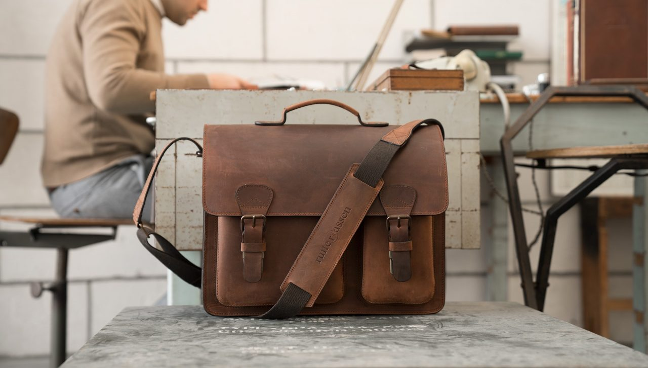 Professor in office with traditionnal brown leather satchel briefcase.