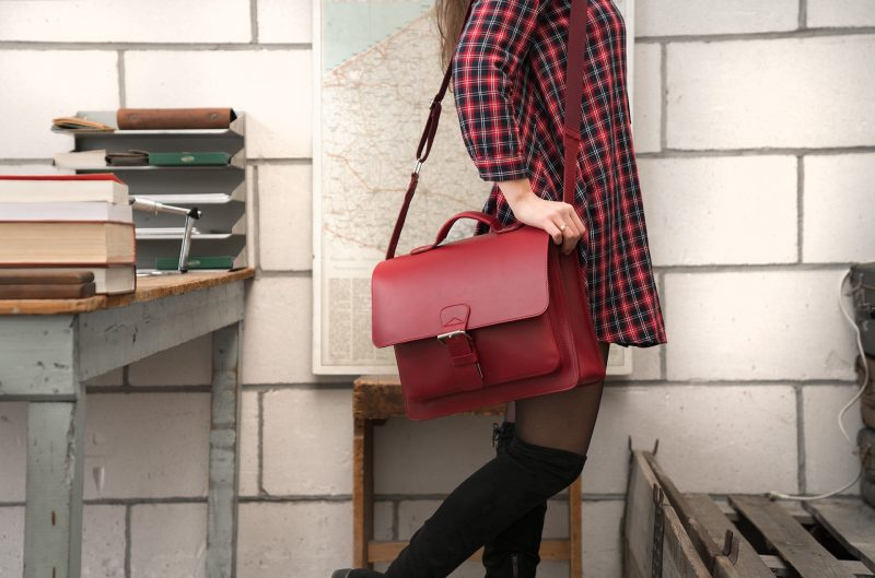 Student carrying red leather briefcase with single compartment and large front pocket - 152141.