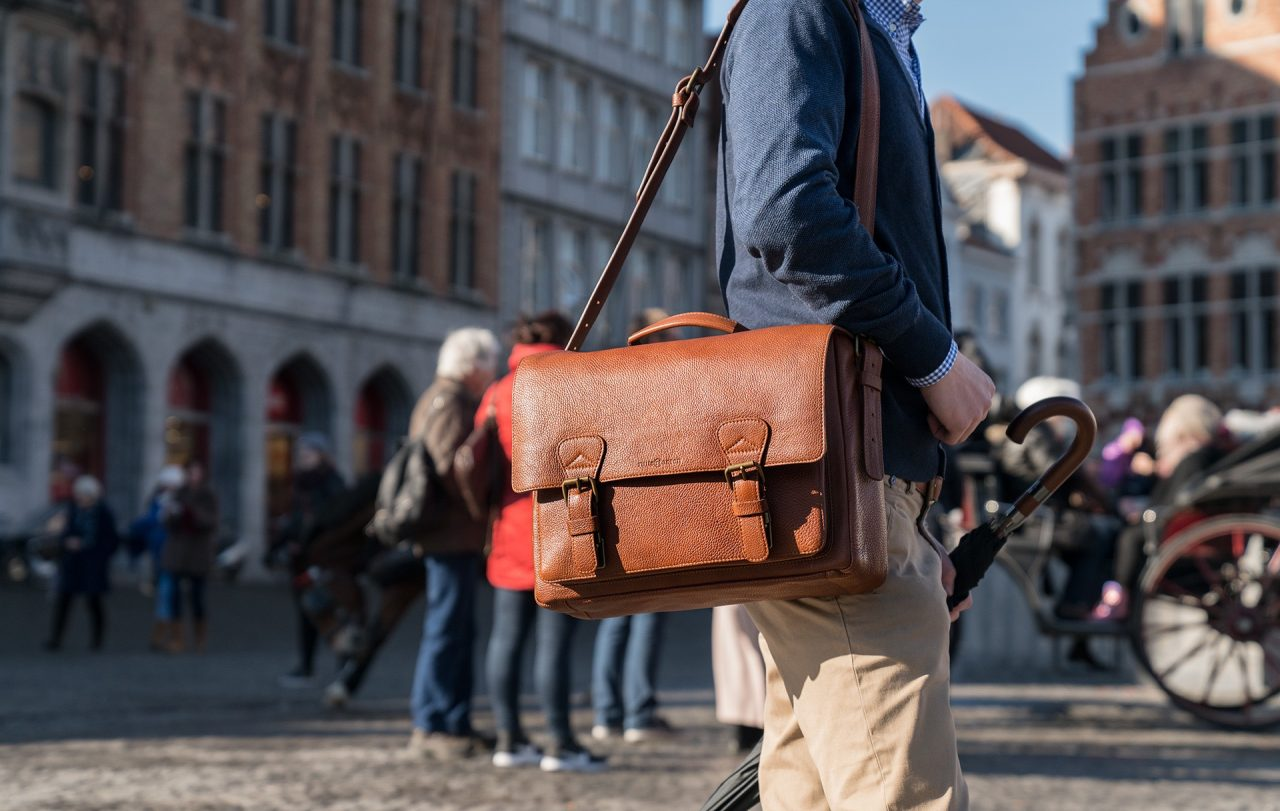 """Man wearing the 13"""" soft leather satchel briefcase."""