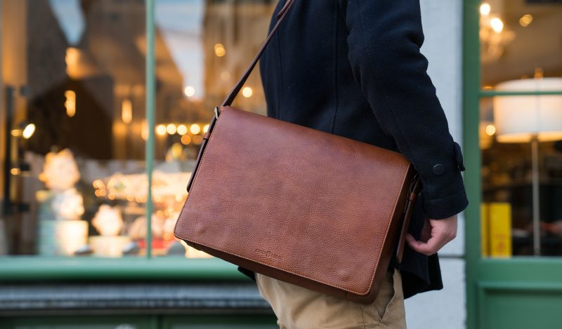 """Man wearing the 13"""" soft leather messenger bag."""