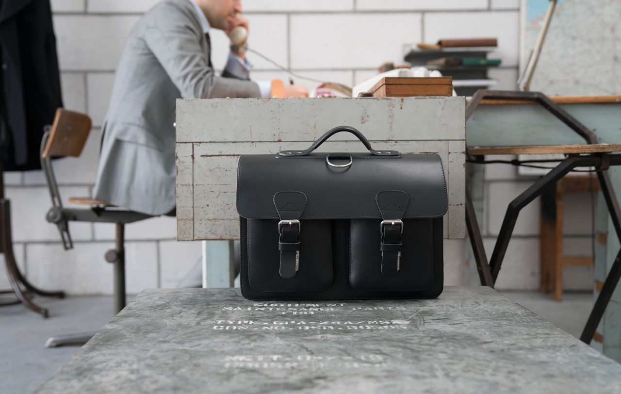 Man in office with black leather satchel backpack for adults with 2 gussets and symmetric front pockets 112233.