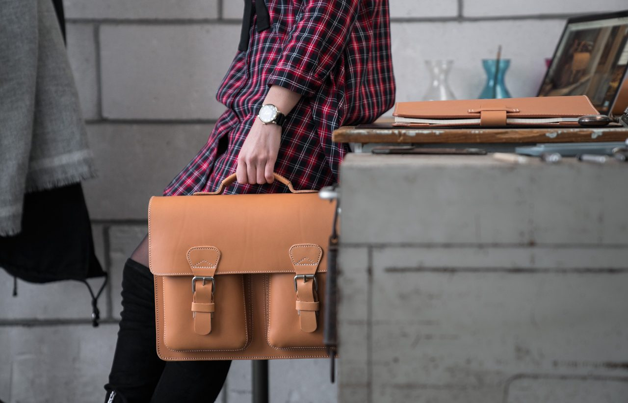 Woman holding her tan leather satchel briefcase by the handle in her office.