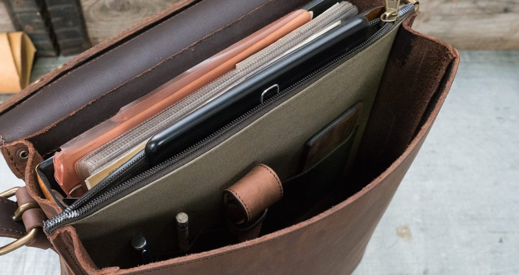 Top view of the vegetable-tanned brown leather backpack with tablet.