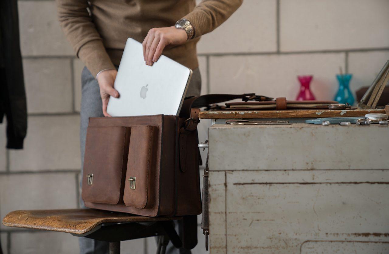 Man fitting his macbook in his large Ruitertassen brown leather satchel.