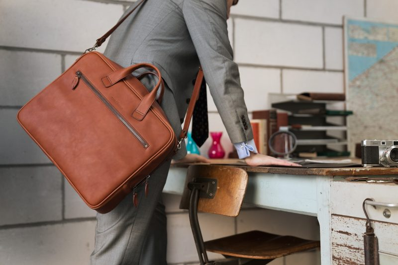 Man wearing the luxury brown vegetable-tanned leather briefcase in office.