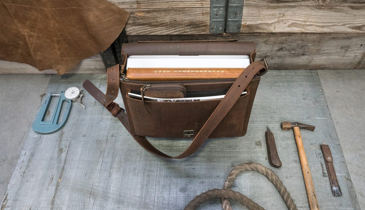 Open brown leather briefcase with folder, macbook computer, book and pencil case.