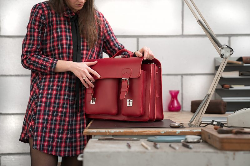 Student in office opening her red leather satchel backpack with 2 gussets and asymmetric front pockets for women - 152237.