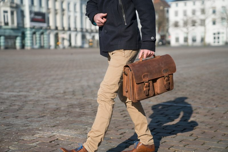 Professor carrying his vintage brown leather satchel by the handle in the street.