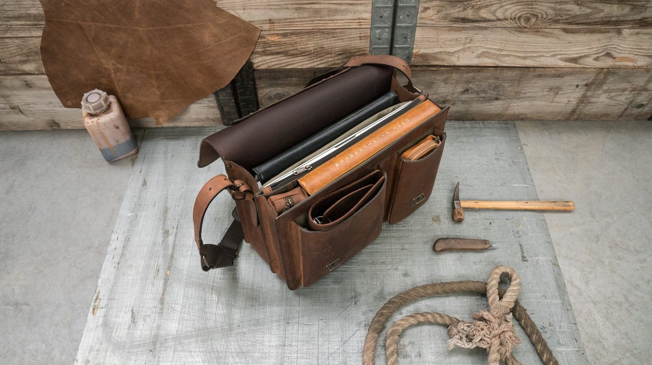 Open full grain brown leather satchel with laptop pocket and folders.