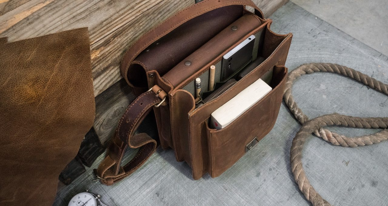 Top view of the handmade vegetable-tanned brown leather crossbody bag for men.