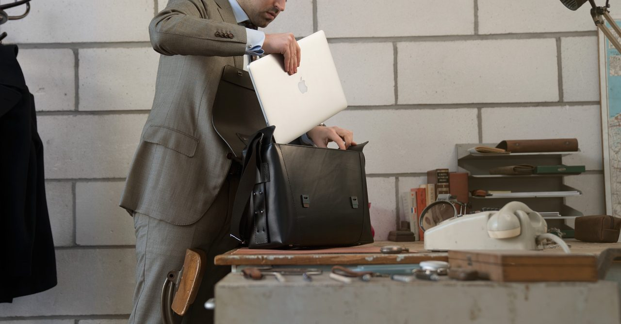 Man fitting his laptop in the large black vegetable-tanned leather briefcase bag with laptop pocket.