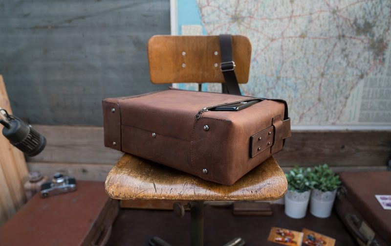 Back view of the large vegetable-tanned brown leather briefcase bag with tablet in back pocket.