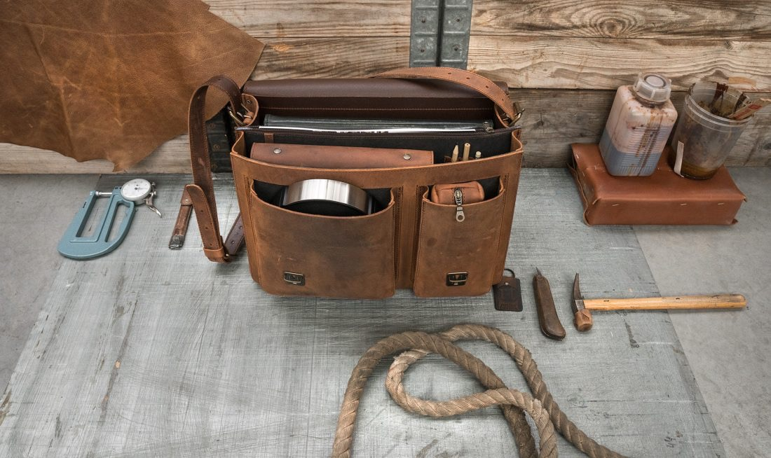 Open full-grain brown leather satchel for professionals with folders and accessories.