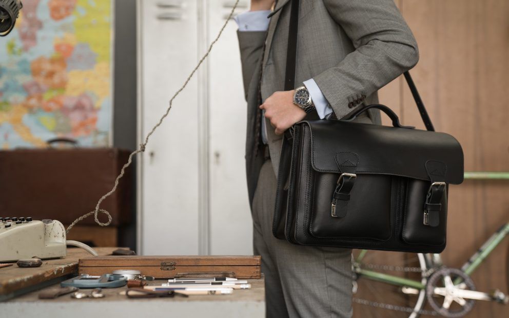 Man carrying his black leather satchel briefcase with asymmetric front pockets on the shoulder.