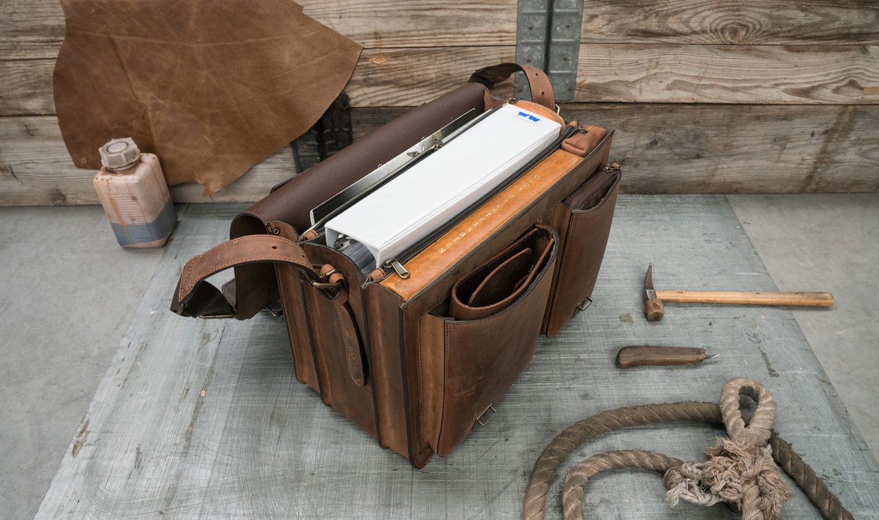 Open large brown leather satchel with large folder and macbook laptop.