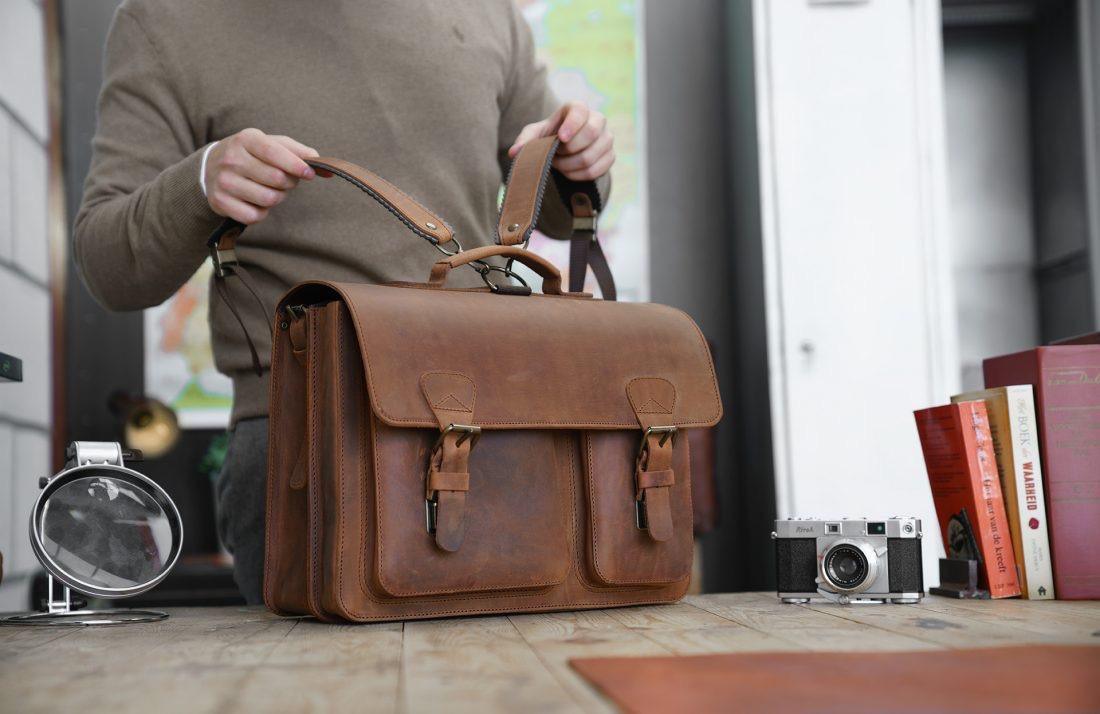 Professor preparing his Ruitertassen vintage brown leather satchel with shoulder straps.
