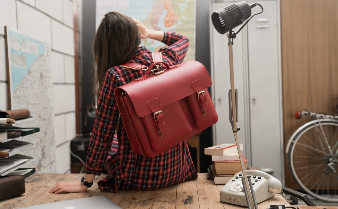 Student carrying her red leather satchel backpack with 2 gussets and asymmetric front pockets for women - 152237.
