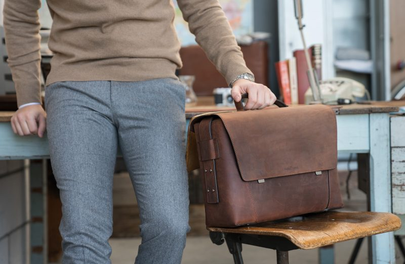 Man holding the large vegetable-tanned brown leather briefcase bag with laptop pocket.