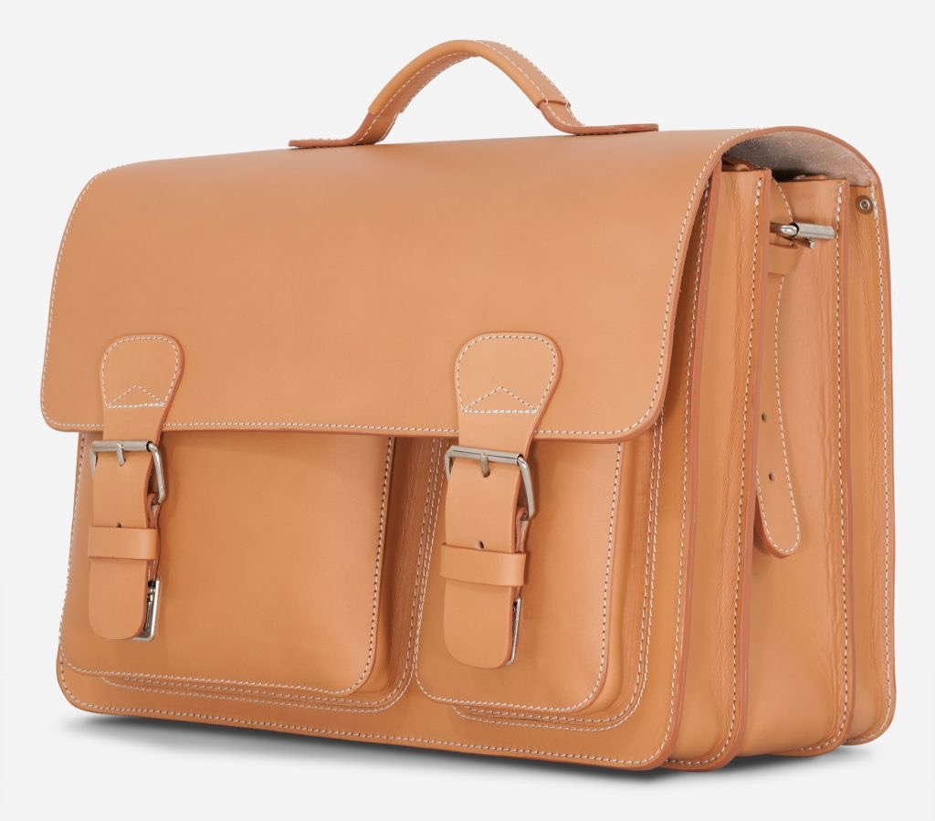 Side view of large tan leather satchel with 3 compartments and front pockets.