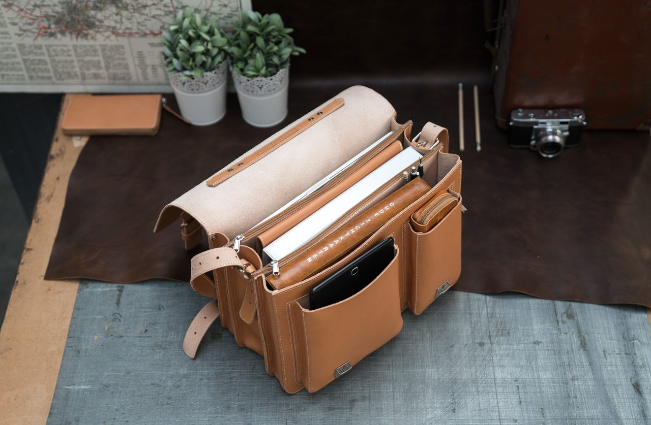 Open tan leather satchel briefcase with laptop computer, leather folio, files, tablet and pencil case.