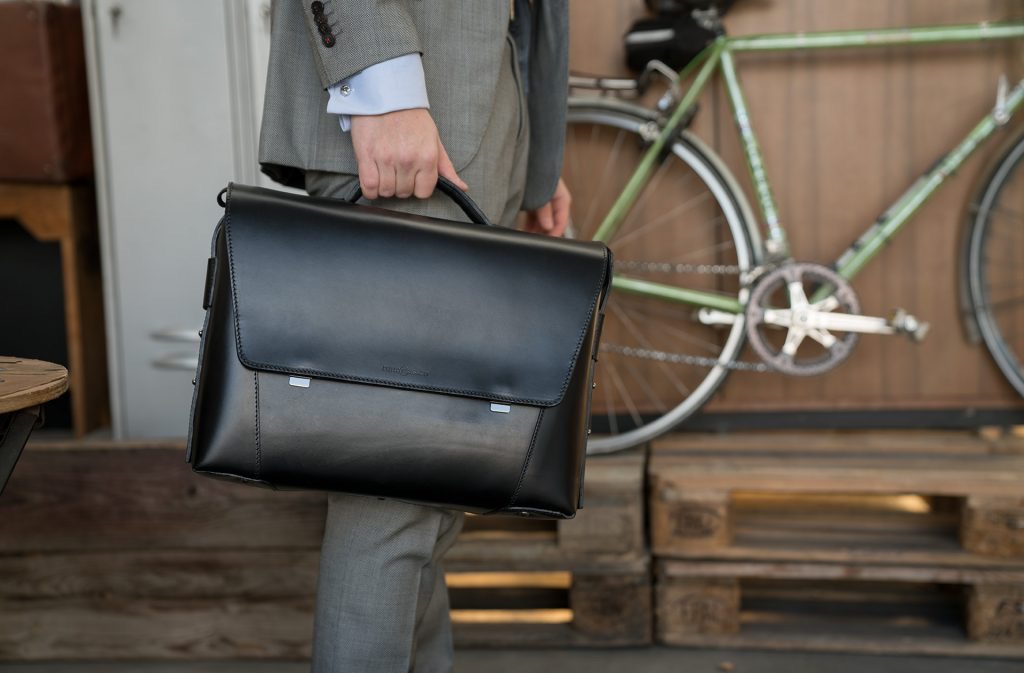 Man holding the large black vegetable-tanned leather briefcase bag with laptop pocket.
