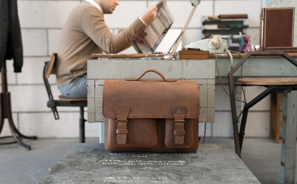Man in office with vintage brown leather satchel briefcase.
