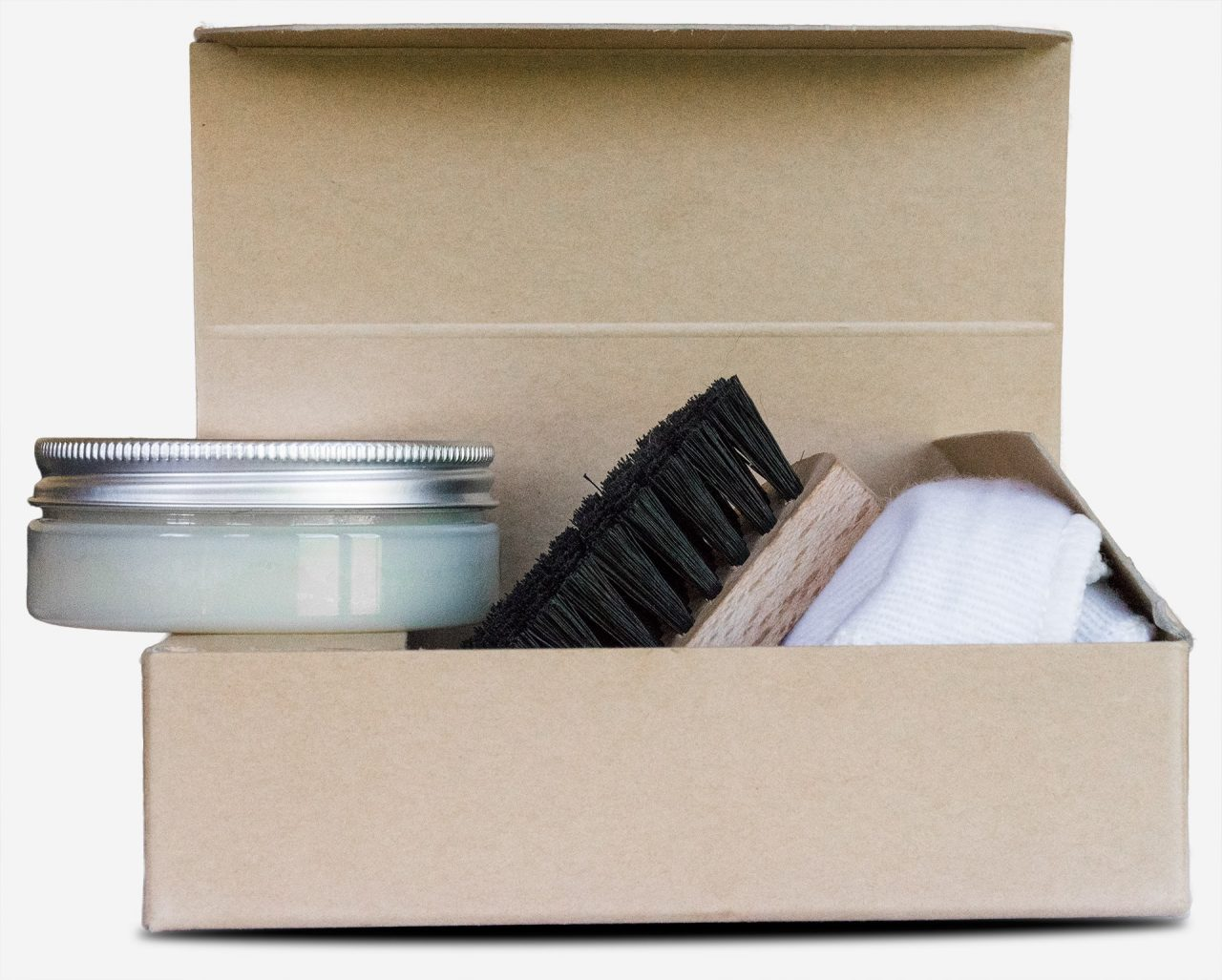 Wax for vegetable-tanned leather in care kit with brush and soft cloth.