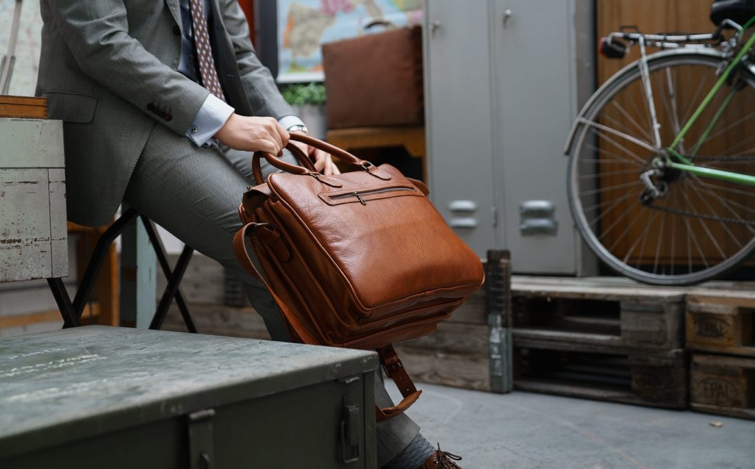 """Man wearing the 17"""" brown soft leather travel bag."""