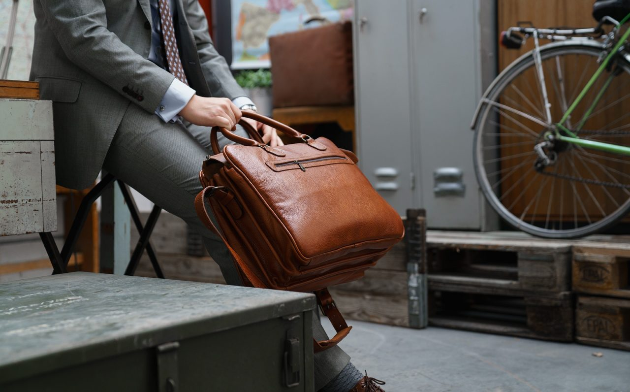 "Man wearing the 17"" brown soft leather travel bag."