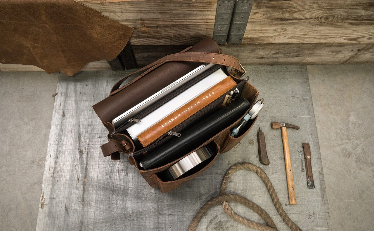 Open brown leather satchel briefcase with laptop computer, leather folio, files, tablet and pencil case.
